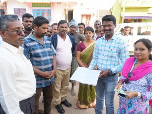 Man holding register with fees paid by water users in India